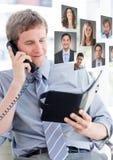 Bemannen Sie das Halten des Telefons und treten Sie mit Buch mit Profilporträts von Leuten in Verbindung Lizenzfreie Stockbilder