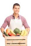 Bemannen Sie das Halten einer hölzernen Kiste voll vom Gemüse stockfotos