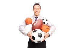 Bemannen Sie das Halten eines Bündels der unterschiedlichen Art von Sportbällen Stockbild