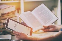 Bemannen Sie das Halten eines modernen ebook Lesers und des Buches in der Bibliothek Lizenzfreies Stockbild