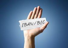 Bemannen Sie das Halten eines Papierfetzens mit - IBAN/BIC Stockfotografie