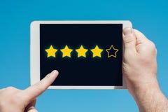 Bemannen Sie das Halten eines Tablettengerätes und das Veranschlagen von Sternen als Bewertung, Rang stockbilder