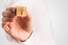 Bemannen Sie das Halten eines Würfels mit einer von Hand gezeichneten Glühlampe Lizenzfreie Stockbilder