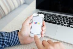 Bemannen Sie das Halten eines weißen iPhone 5s mit APP EBay auf dem Schirm über t Lizenzfreies Stockbild