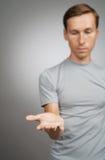 Bemannen Sie das Halten etwas leer in seiner Hand auf einem grauen Hintergrund stockfoto