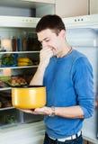 Bemannen Sie das Halten ihrer Nase wegen des schlechten Geruchs vom Lebensmittel lizenzfreie stockbilder