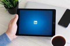 Bemannen Sie das Halten iPad des grauen Services LinkedIn des Sozialen Netzes Proraumes stockfoto