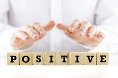 Bemannen Sie das Halten seiner Hände über dem Wort Positiv stockfotos