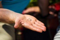 Bemannen Sie das Halten in seiner Hand eines Ringes, der Kerl gibt dem Mädchen einen Ring, a stockfotografie