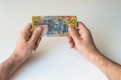 Bemannen Sie das Halten von fünfzig australischem Dollar in seinen Händen Lizenzfreie Stockbilder