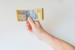 Bemannen Sie das Halten von fünfzig australischem Dollar in seinen Händen Stockfotos