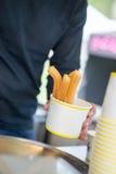 Bemannen Sie das Halten von Papier-cupt gefüllt mit Bonbon gebratenen churros Stockbild