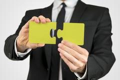 Bemannen Sie das Halten von zwei Stücken eines gelben Puzzlespiels Stockbild