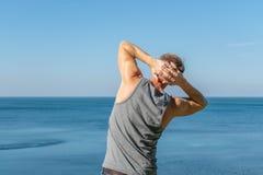 Bemannen Sie das Handeln einer Aufwärmenübung auf dem Ozean Frischluft und ein gesunder Lebensstil lizenzfreie stockfotografie