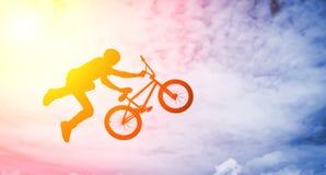 Bemannen Sie das Handeln eines Sprunges mit einem bmx Fahrrad. Lizenzfreie Stockfotos