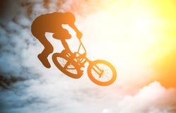 Bemannen Sie das Handeln eines Sprunges mit einem bmx Fahrrad. Stockfotos