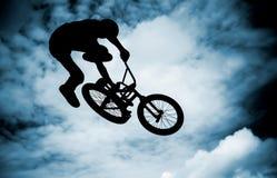 Bemannen Sie das Handeln eines Sprunges mit einem bmx Fahrrad. Lizenzfreie Stockfotografie
