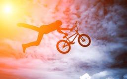 Bemannen Sie das Handeln eines Sprunges mit einem bmx Fahrrad. Stockfoto