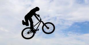 Bemannen Sie das Handeln eines Sprunges mit einem bmx Fahrrad Stockfoto