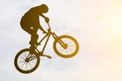 Bemannen Sie das Handeln eines Sprunges mit einem bmx Fahrrad Stockfotografie