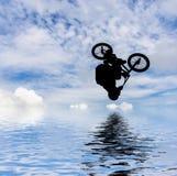 Bemannen Sie das Handeln eines Sprunges mit einem bmx Fahrrad Lizenzfreies Stockbild