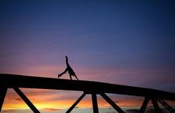 Bemannen Sie das Handeln eines Wagenrads auf Stahlbrücke bei Sonnenuntergang lizenzfreies stockbild