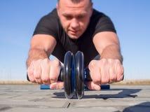 Bemannen Sie das Handeln von Übungen mit einem Machtrad im Freien stockbild