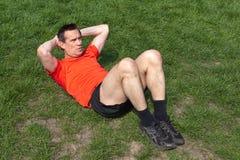 Bemannen Sie das Handeln von Situps auf dem Gras Stockbilder