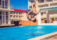Bemannen Sie das Handeln von Somersaul oder schlagen Sie Tauchen in Swimmingpool leicht Stockfoto