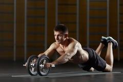 Bemannen Sie das Handeln von Sportübung auf Boden mit dem Tonen des Rades Lizenzfreie Stockfotografie