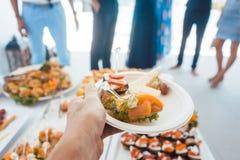 Bemannen Sie das Helfen auf dem Buffet der Partei Lebensmittel draußen nehmend Stockfotos