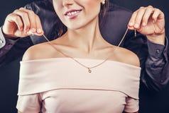 Bemannen Sie das Helfen seiner Freundin, eine goldene Halskette an zu versuchen Geschenk für Valentinstag stockfotografie