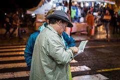 Bemannen Sie das Helfen zu einem Touristen, einen Standort in einer Papierkarte auf der Straße zu finden lizenzfreie stockfotos