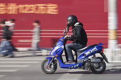 Bemannen Sie das Hetzen auf einem Roller mit Anschlagtafel auf Hintergrund, Peking, China Stockfoto
