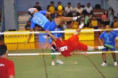 Bemannen Sie das Highblocking den Ball durch das Netz im Spiel des Tritt-Volleyball, sepak takraw Stockfoto