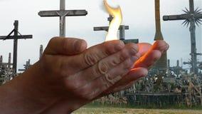 Bemannen Sie das Holen des Feuers, das in den Waffen mit Kreuzhintergrund brennt stock video footage