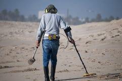 Bemannen Sie das Kämmen des Strandes mit einem Metalldetektor Stockbild