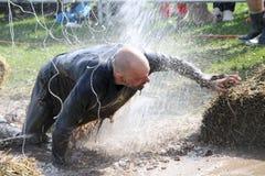 Bemannen Sie das Kämpfen, zum durch den Schlamm zu erhalten, gespritzt mit Wasser, elektrisch Stockfotografie
