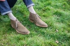 Bemannen Sie das Kühlen auf tragenden Schuhen und Jeans des grünen Grases lizenzfreies stockfoto