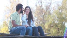 Bemannen Sie das Küssen der Frau auf einer Backe während sie hörend Musik auf Kopfhörern stock footage