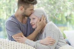 Bemannen Sie das Küssen seiner kranken Freundin auf der Stirn Unterstützung während stockfotos