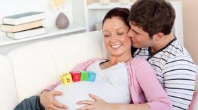 Bemannen Sie das Küssen seiner schwangeren Frau mit Schätzchenzeichen Lizenzfreie Stockfotografie