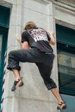 Bemannen Sie das Klettern einer Hausmauer auf Straßenflusssteinwettbewerb Lizenzfreie Stockfotografie