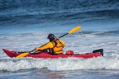 Bemannen Sie das Kämpfen der Welle auf Kajak auf rauem Meer Stockfoto