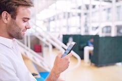 Bemannen Sie das Lächeln während Mitteilung auf seinem neuen modernen Smartphone Stockfoto
