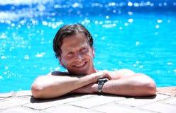 Bemannen Sie das Lügen auf Seite des Swimmingpools in der Sonne Stockbild