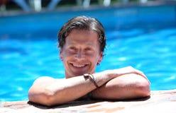 Bemannen Sie das Lügen auf Seite des Swimmingpools in der Sonne Stockfoto