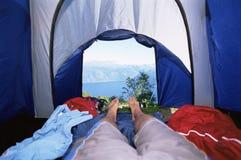 Bemannen Sie das Lügen im Zelt mit einer Ansicht von See Stockfotos