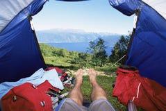 Bemannen Sie das Lügen im Zelt mit einer Ansicht von See Lizenzfreies Stockfoto