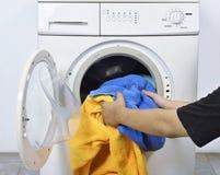 Bemannen Sie das Laden der schmutzigen Tücher in Waschmaschine für gewaschen lizenzfreies stockbild